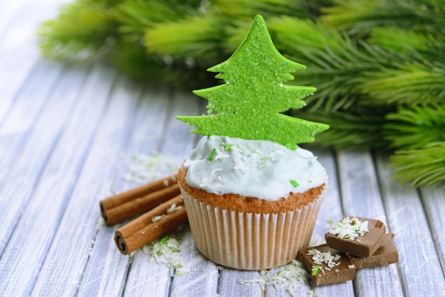 Leckerer cupcake mit buttercreme, auf farbigem holzhintergrund