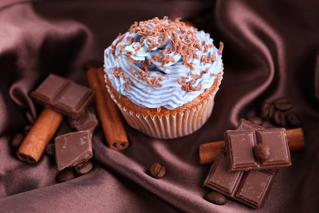 Leckerer cupcake mit buttercreme, auf farbigem stoffhintergrund