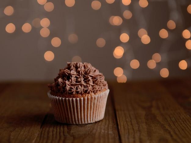 Leckerer cupcake mit buttercreme auf holztisch mit defokussierten lichtern