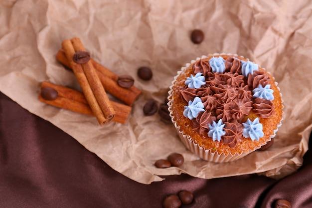 Leckerer cupcake mit buttercreme auf zerknittertem papier