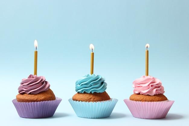 Leckerer cupcake mit einer kerze auf farbigem hintergrund mit platz zum einfügen von text. festlicher hintergrund, geburtstag. foto in hoher qualität