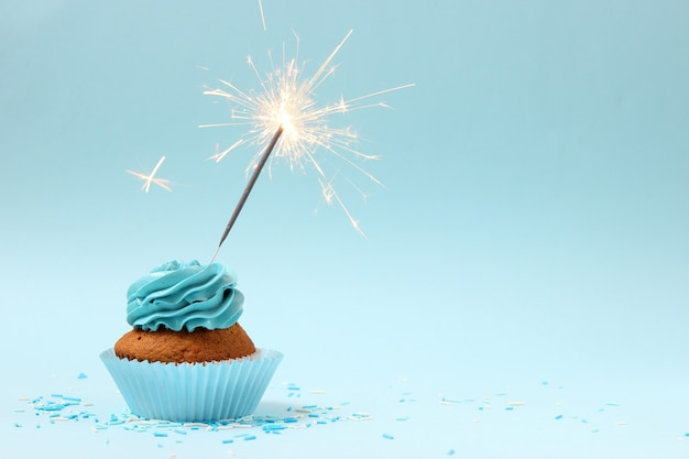 Leckerer cupcake mit kerze auf farbigem hintergrund