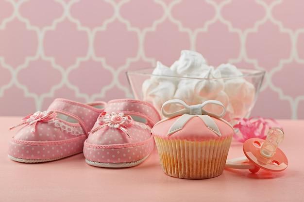 Leckerer cupcake mit schleife und babyschuhen, schnuller auf farbigem hintergrund