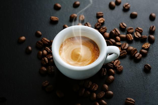 Leckerer dampfender espresso in einer tasse mit kaffeebohnen. von oben betrachten. dunkler hintergrund.