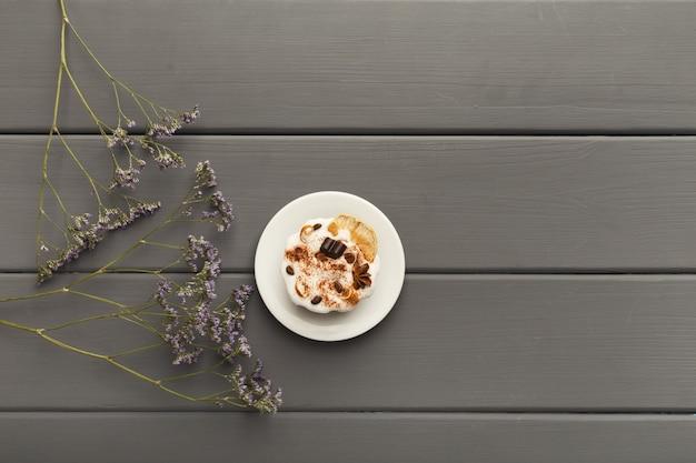Leckerer desserthintergrund. schokoladenkuchen auf grauem rustikalem tisch mit violetten blumen, provence-stil, draufsicht, kopierraum