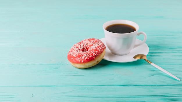 Leckerer donut mit tasse tee und löffel auf grüner tabelle