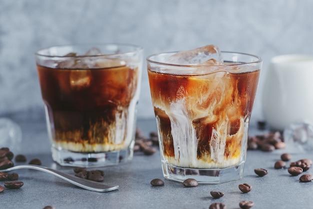 Leckerer erfrischender eiskaffee mit eiswürfeln in gläsern auf hellem hintergrund. nahaufnahme