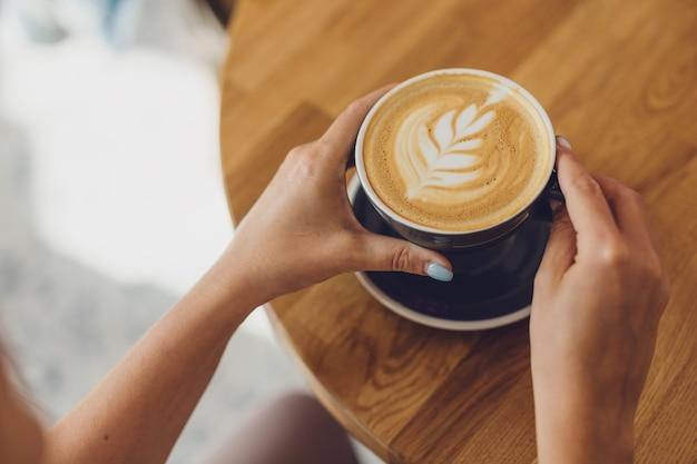 Leckerer frischer cappuccino in der tasse auf holztisch. nicht erkennbare frau, die tasse in den händen hält.