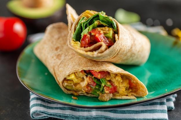 Leckerer frischer veganer vegetarischer wrap mit spinat, tomate, avocado auf teller serviert.