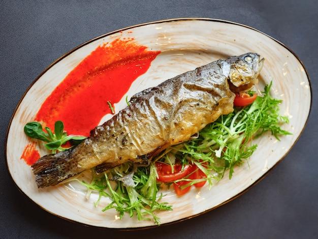 Leckerer gebackener fisch in weißer platte auf holztisch. ansicht von oben
