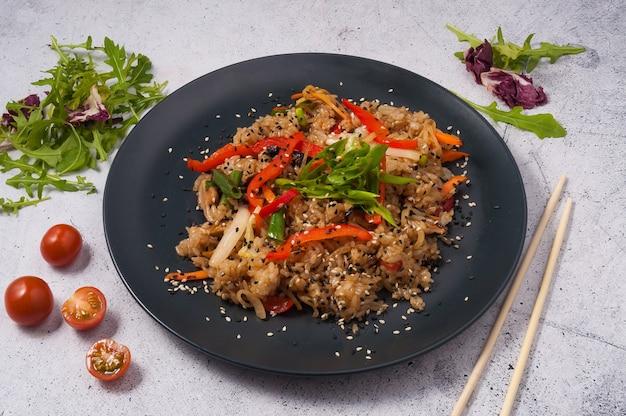Leckerer gebratener reis mit gemüse auf einem schwarzen teller. asiatische küche
