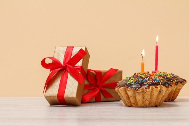 Leckerer geburtstagsmuffin mit schokoladenglasur und karamell, dekoriert mit brennender festlicher kerze und geschenkboxen mit roten bändern auf beigem hintergrund. alles gute zum geburtstag minimales konzept.
