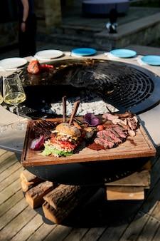 Leckerer gegrillter burger auf kettle grill pit mit gusseisenrost zubereitet. runde tisch-kochfläche. bbq hot grill mit edelstahlgitter auf backyard ready grilling cookout essen. grillen mit flammen