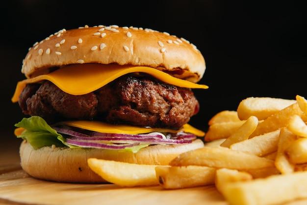 Leckerer gegrillter großer cheeseburger mit pommes frites auf holzbrett. nahansicht. premium foto