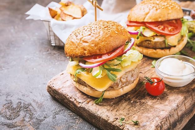 Leckerer gegrillter klassischer rindfleischburger mit salat und mayonnaise-sauce auf einem rustikalen holztisch mit kopierraum
