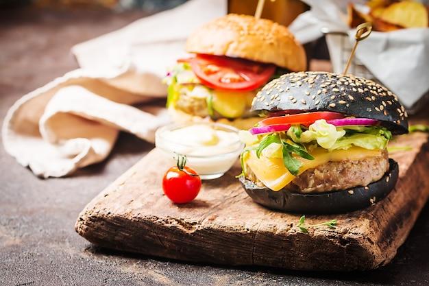 Leckerer gegrillter klassischer schwarzer rindfleischburger mit salat und mayonnaise-sauce auf einem rustikalen holztisch mit kopierraum