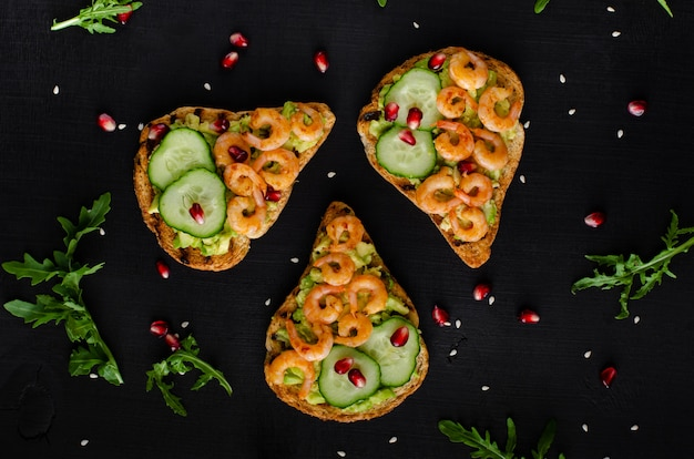 Leckerer, gesunder snack mit avocado-toast, gurke und garnelen. flachgelegt, draufsicht.