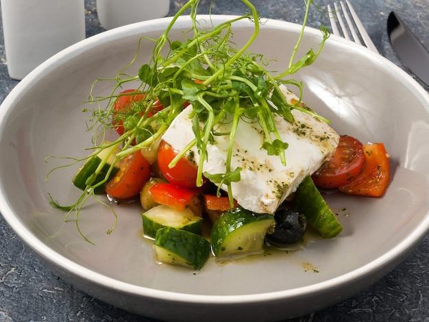 Leckerer griechischer salat mit einem ganzen stück käse und mikrogrün