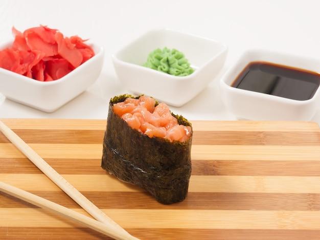 Leckerer gunkan mit lachs auf japanischer küche mit holzbrett