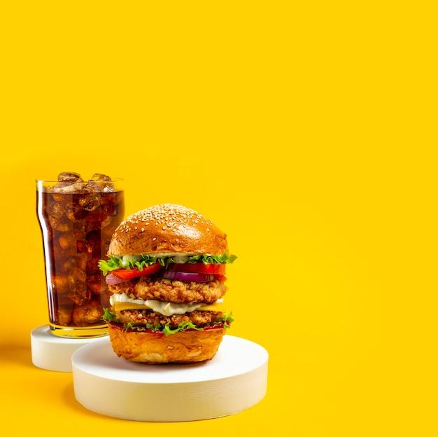 Leckerer hamburger mit cola auf gelbem grund