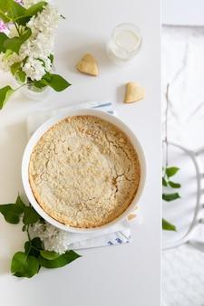 Leckerer hausgemachter käsekuchen in weißer schale auf einem tisch mit flieder