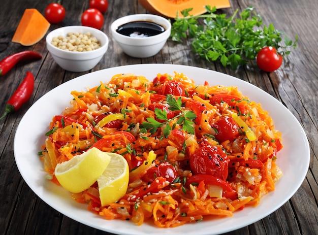Leckerer heißer kürbissalat mit tomaten, paprika, zwiebeln, sesam und pinienkernen