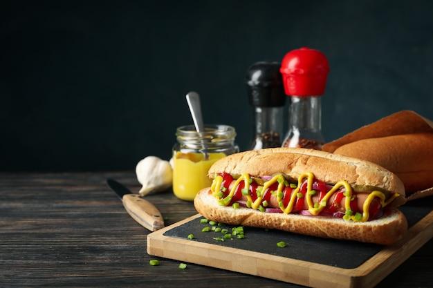 Leckerer hot dog und zutaten auf holzoberfläche