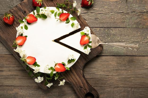 Leckerer käsekuchen mit erdbeeren auf einem hölzernen hintergrund. schöne komposition