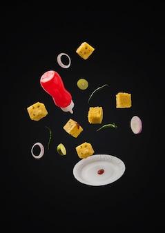 Leckerer khaman dhokla, der mit ketchup-flasche, grünem chili, zitrone und teller über einfarbigem hintergrund fliegt