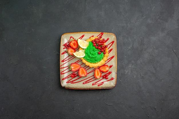 Leckerer kuchen der draufsicht mit grüner sahne und erdbeeren auf dem süßen hintergrunddesserttee des dunklen hintergrunds