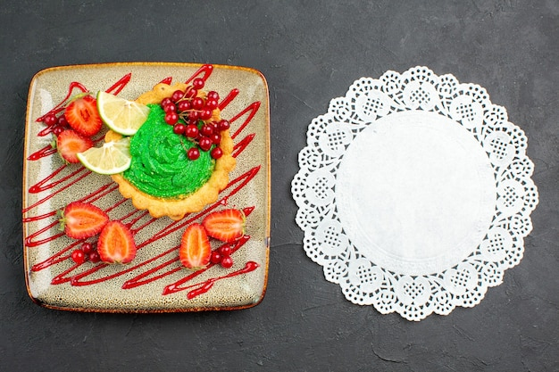 Leckerer kuchen der draufsicht mit grüner sahne und erdbeeren auf süßem desserttee des dunklen schreibtisches