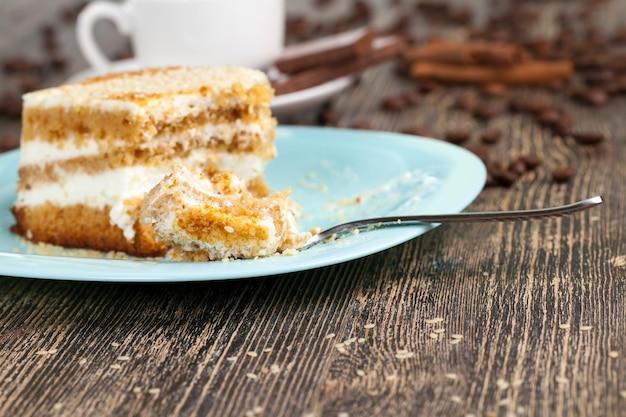 Leckerer kuchen in stücke geschnitten, mehrschichtiger teig mit buttercreme, dessert mit vielen kalorien, kuchen nahaufnahme