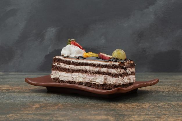 Leckerer kuchen mit früchten auf teller auf marmortisch.