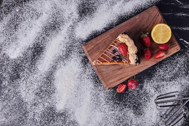 Leckerer kuchen mit früchten neben dem mixer auf holzbrett.
