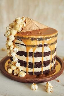 Leckerer kuchen mit karamellcreme und einer mit popcorn gefüllten tüte drauf