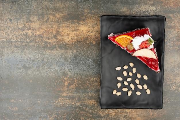 Leckerer kuchen mit nüssen auf teller auf marmoroberfläche