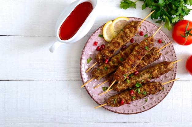 Leckerer lula-kebab auf dem teller auf einem weißen holztisch. gehacktes fleisch auf holzspießen, gegrillt.
