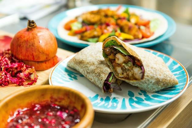Leckerer mexikanischer burrito mit gemüse und brathähnchen auf einem teller