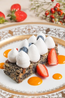 Leckerer mohnkuchen mit sahne-erdbeeren und blaubeeren