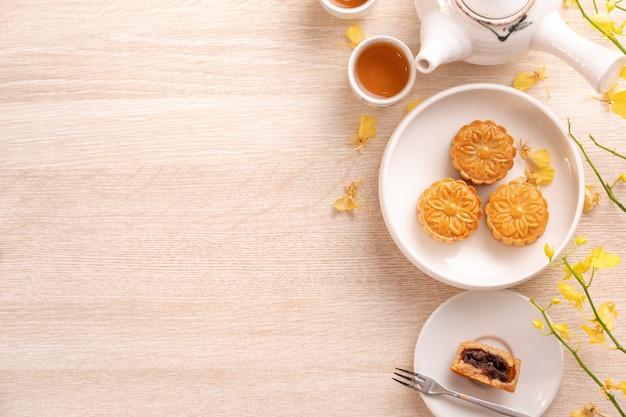 Leckerer mondkuchen für das mittherbstfest mit schönem muster, verziert mit gelben blumen und tee
