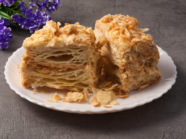 Leckerer napoleon-kuchen ein stück luftiger zarter blätterteig auf einem teller