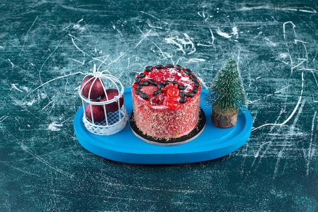 Leckerer obstkuchen mit weihnachtskugeln und weihnachtsbaum. foto in hoher qualität