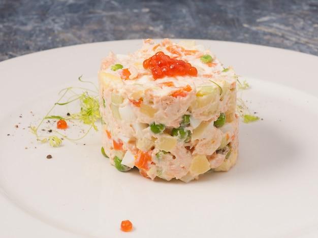 Leckerer olivier-salat mit lachs und rotem kaviar auf einem weißen teller in einem restaurant