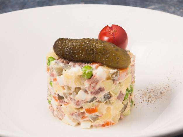 Leckerer olivier-salat mit roastbeef auf einem weißen teller in einem restaurant