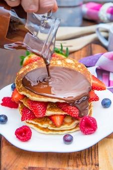 Leckerer pfannkuchen mit frischen beeren und schokolade