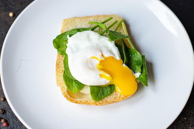 Leckerer pochierter ei-sandwich-spinat auf dem tisch