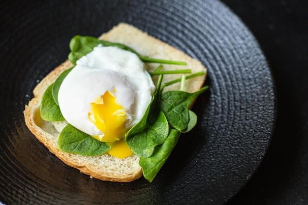 Leckerer pochierter ei-sandwich-spinat