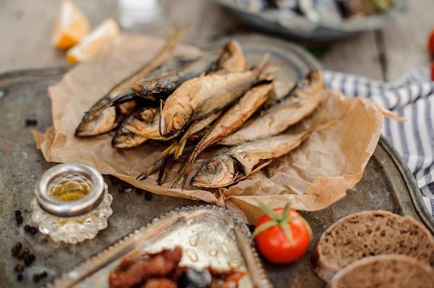 Leckerer rauchgetrockneter stöckerfisch auf dem papier mit sonnengetrockneten und frischen tomaten, öl und brot auf dem metalltablett.