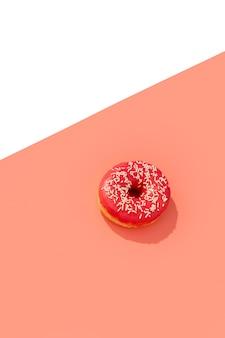 Leckerer rosa donut auf kreativ mit tiefem langem schatten