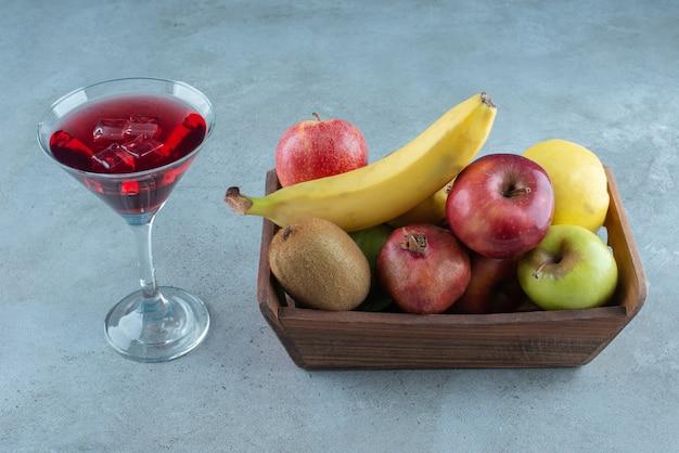 Leckerer saft mit eiswürfeln und verschiedenen früchten.